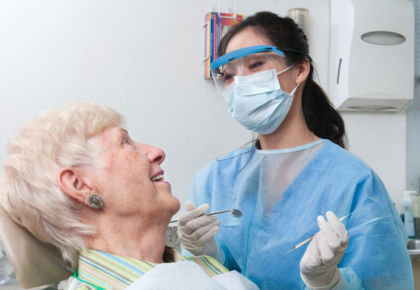 A dental hygienist smiling and talking with an elderly female patient as she prepares to work on her teeth.