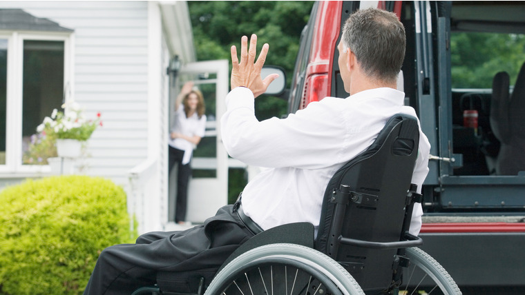 AMBWFR Side profile of a mid adult man sitting in a wheelchair and waving his hand