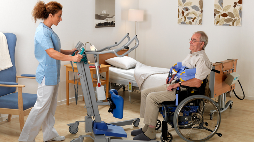 ArjoHuntleigh-Products-Patient-Transfer-Solutions-Standing-and-Raising-Aids-Sara-3000-patient-in-wheelchair-with-slings-attatched-carer
