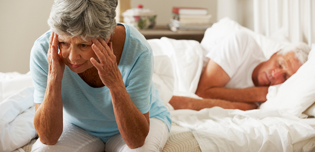 Worried Senior Woman Sits On Bed Whilst Husband Sleeps