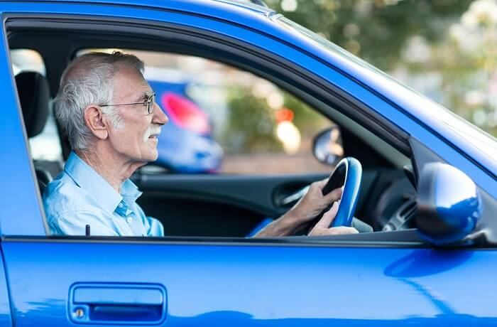 elderly-man-driving-blue-car-main