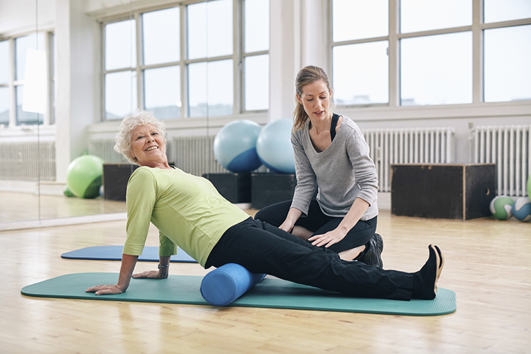 Senior woman doing pilates on the floor with foam roller. Elder woman exercising being assisted by personal trainer at gym.