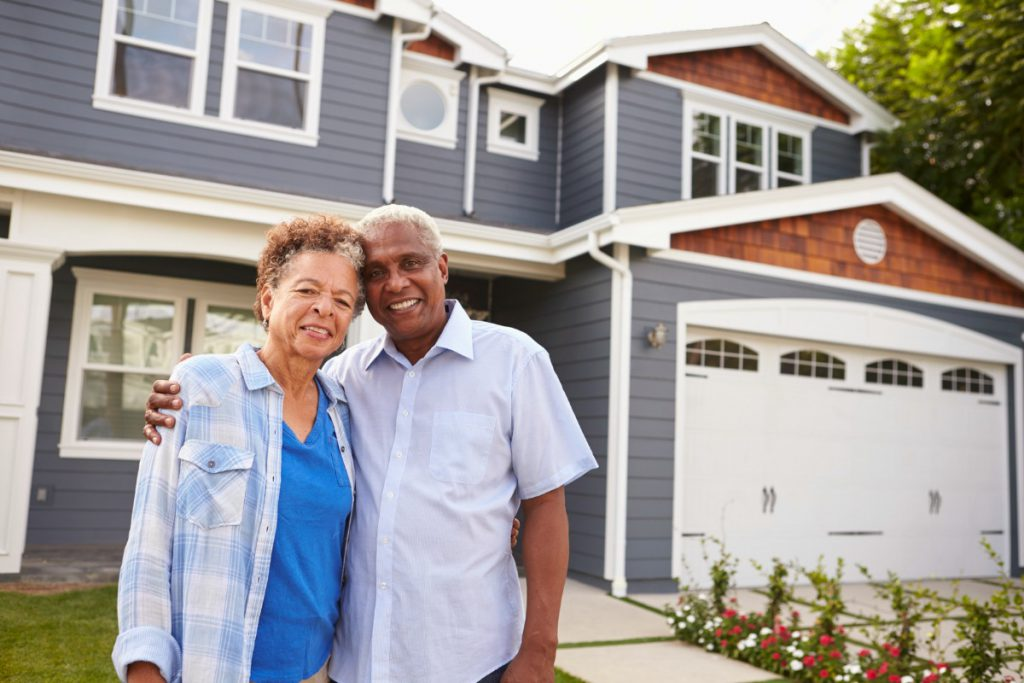 Senior black couple standing outside a large suburban house