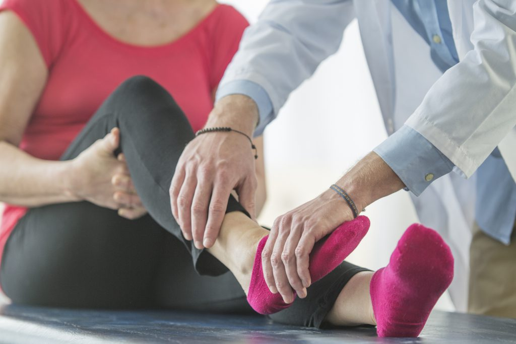 A senior adult woman is at the physical therapists office and if getting her ankle checked.