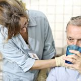 """** ID card is completely created by the photographer. ** Healthcare worker. wearing surgical gloves, checking man's throat as he drinks. She is a Speech Therapist specialising in dysphagia (swallowing) and she is checking the man's swallow as he drinks. She is looking for laryngial extrusian and the movement of the Adam's apple. Neutral tiled background could be in a hospital or could be a home visitMore like this"""