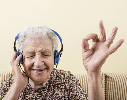 senior woman making okay sign while wearing headphones to listening music