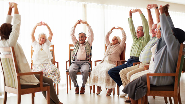 Daily stretching exercise routine for a group of cheerful elderly people at an old age home