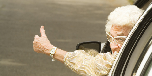 Senior woman giving thumbs up in car