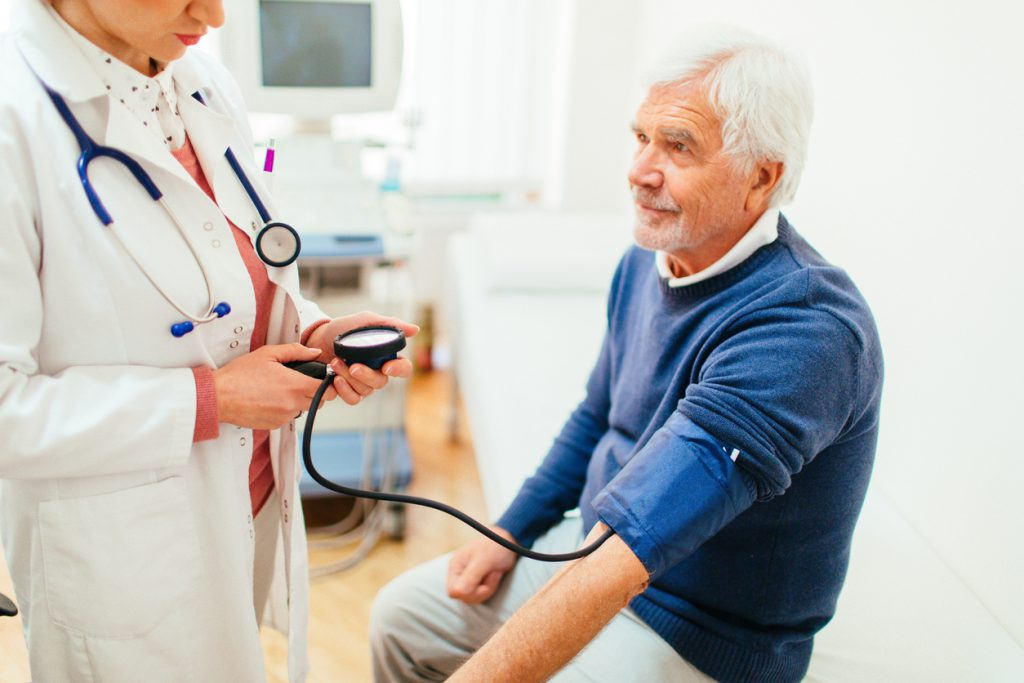An elderly man is being measured for a high blood pressure by his doctor during a medical examination