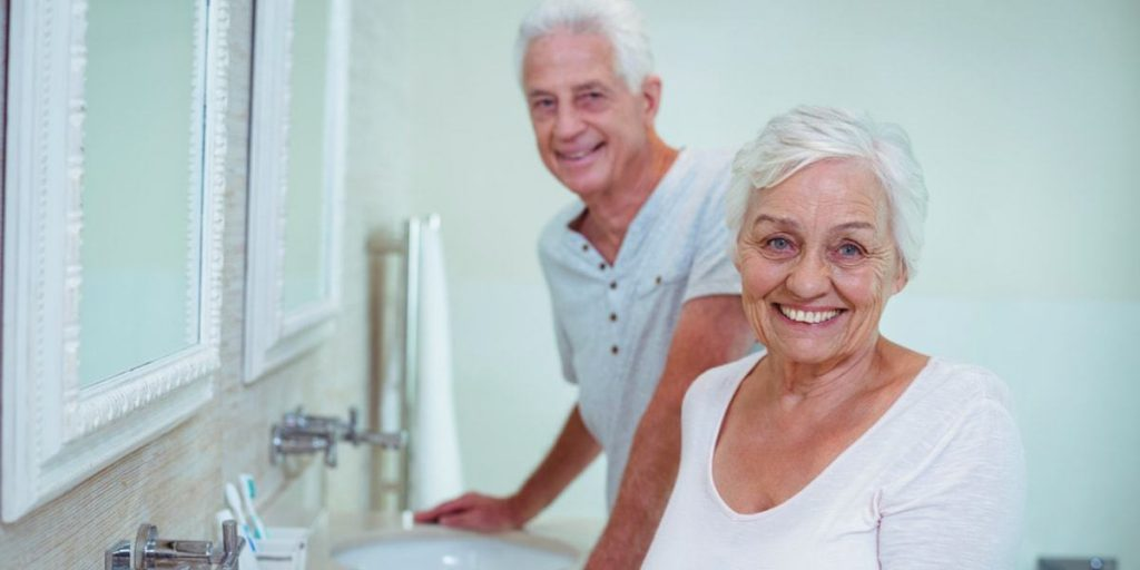 Portrait_of_senior_couple_standing_by_mirror_in_bathroom