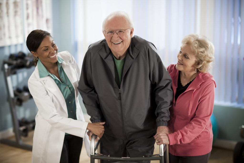 Active senior couple walking with physical therapist.