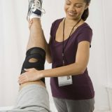 Physical therapist stretching leg of patient